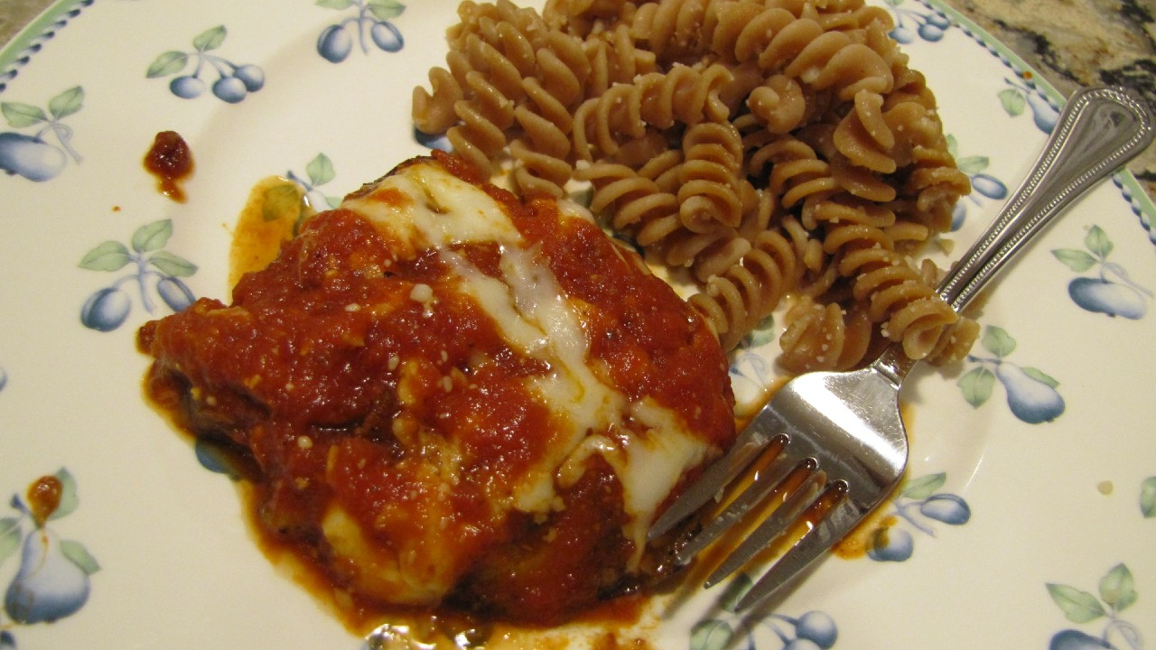 A block of Eggplant Parm with macaroni on a plate with a fork