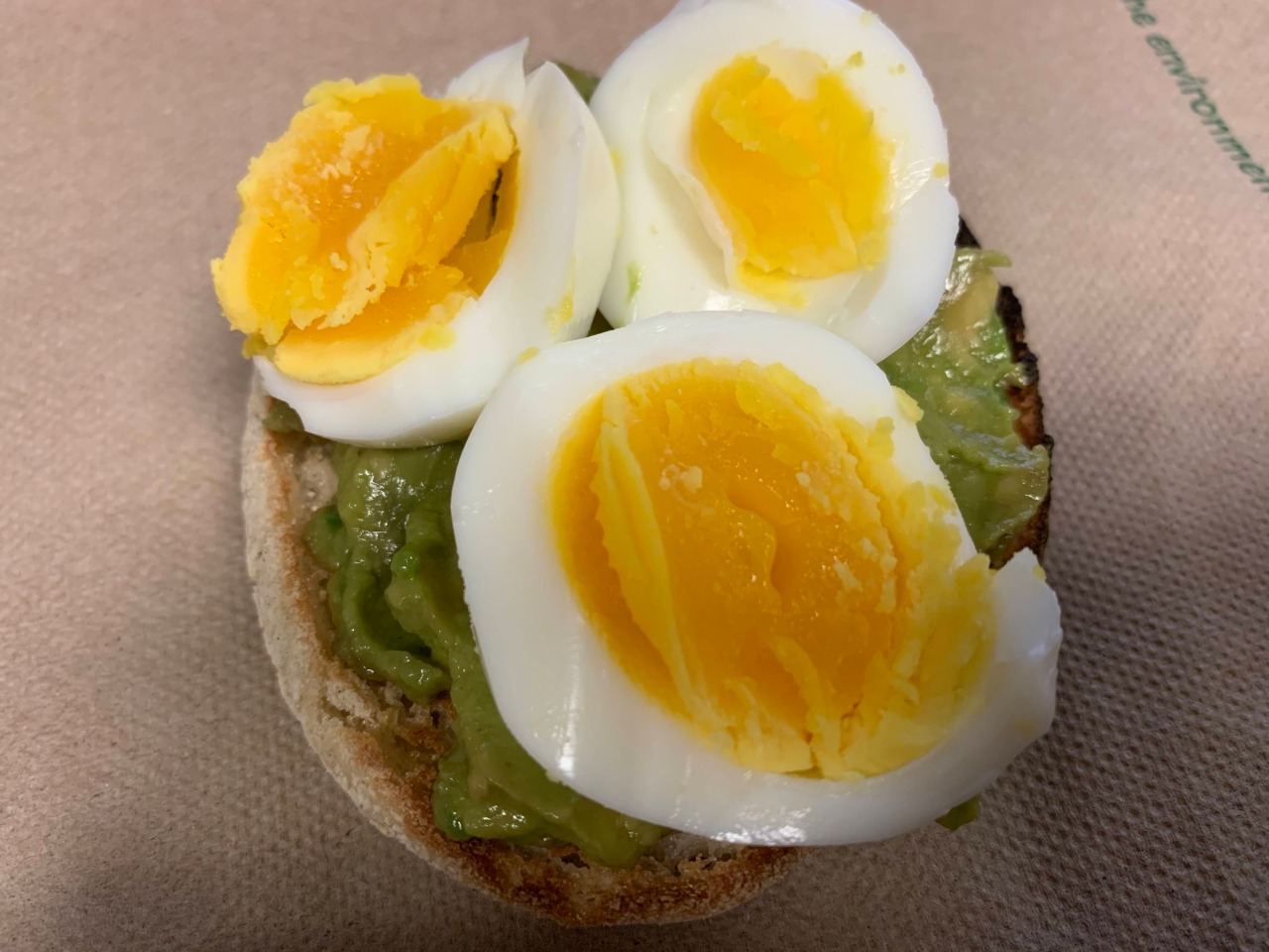 Half an English Muffin with mashed avocado and 3 slices of hard boiled egg