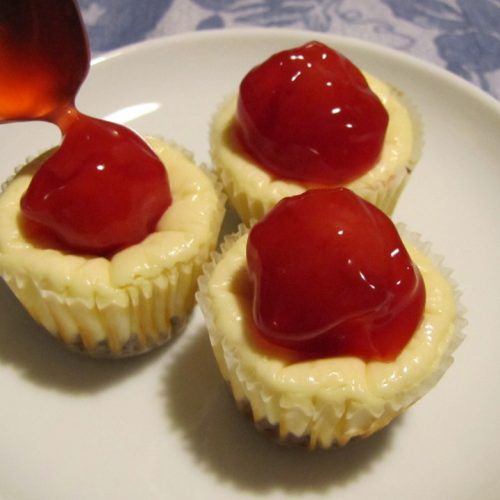 Three mini cheesecake bites on a plate and a spoon and cherry topping