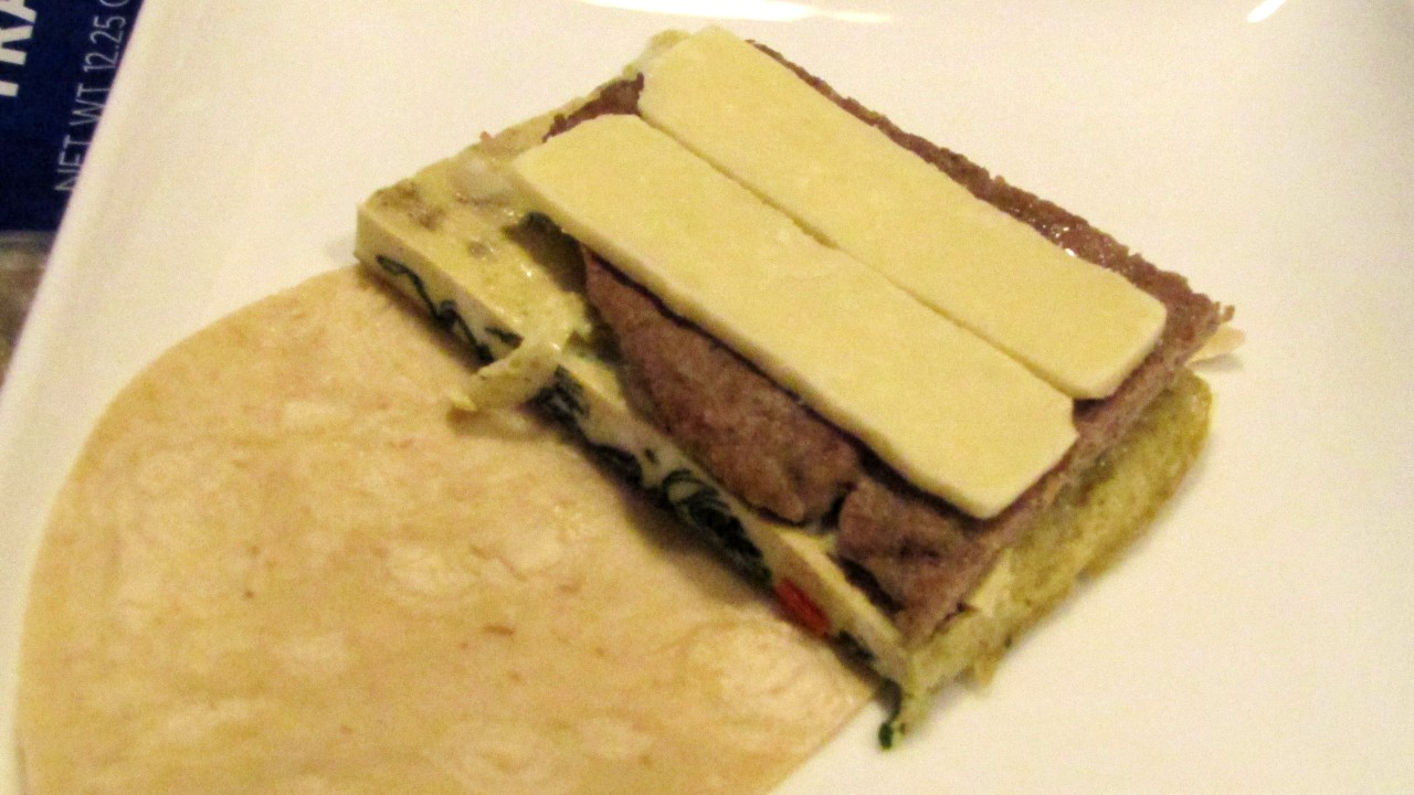 Wrap on a plate with veggie omelet, sausage, and cheese