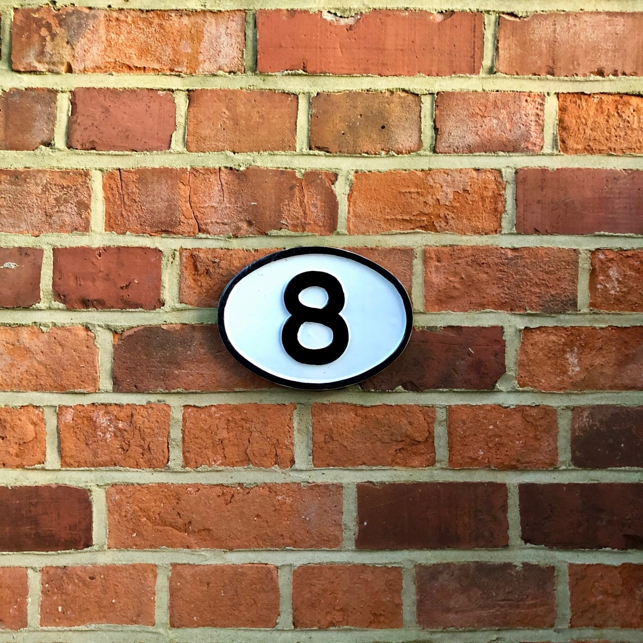 Brick wall with number eight plaque