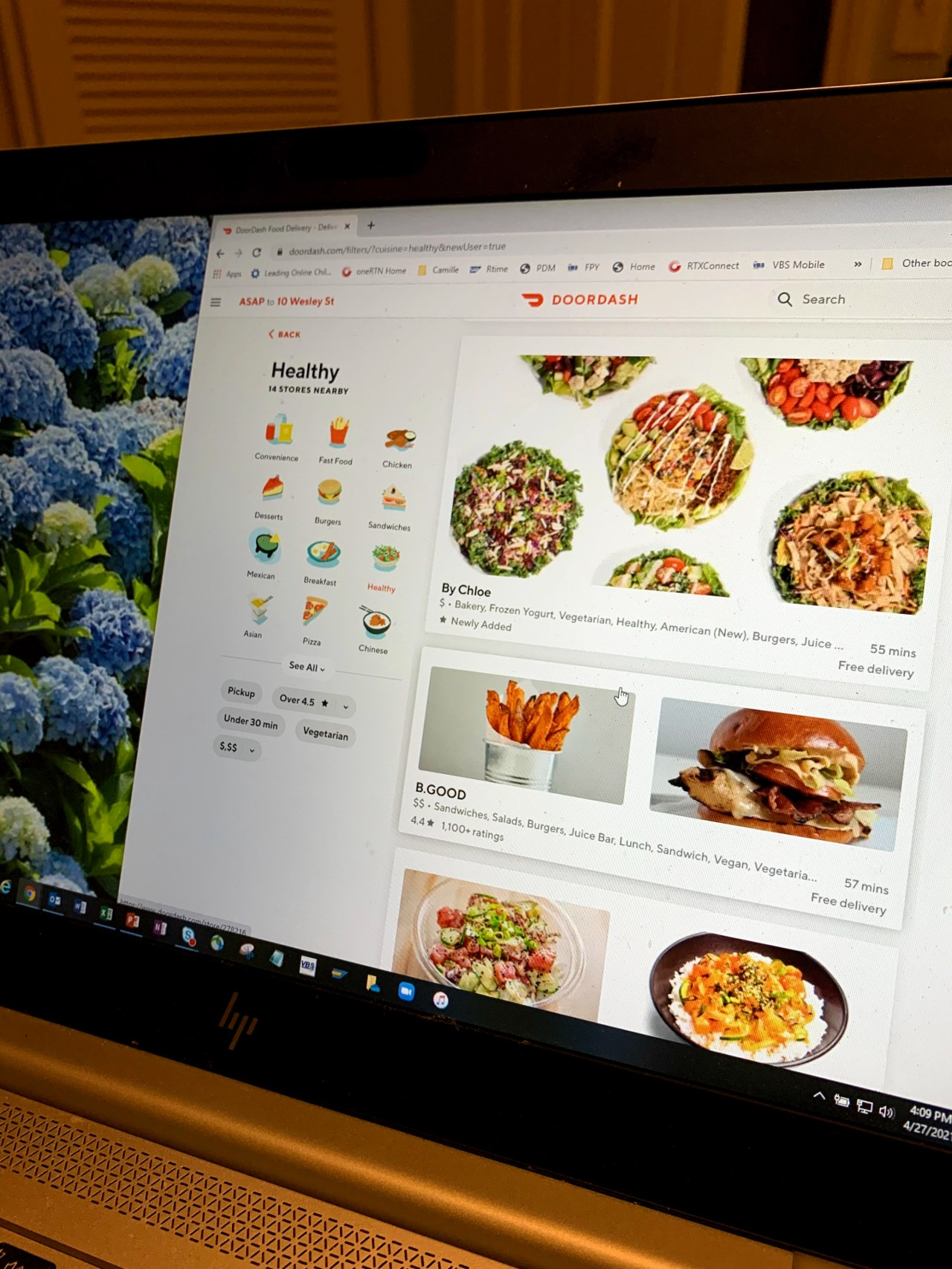 Computer screen showing background of hydrangea and Doordash webpage with healthy foods